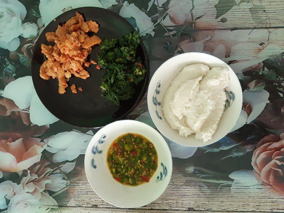 Tradiční africký oběd, zahrnující zeleninu, masovou směs a kaši.