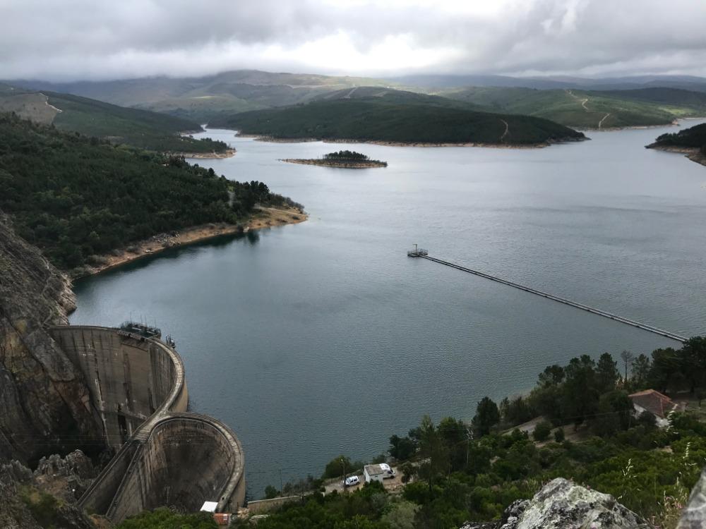 Pohled na přehradu Barragem de Santa Luzia, zatažené nebe, na pozadí hořy a bouřka