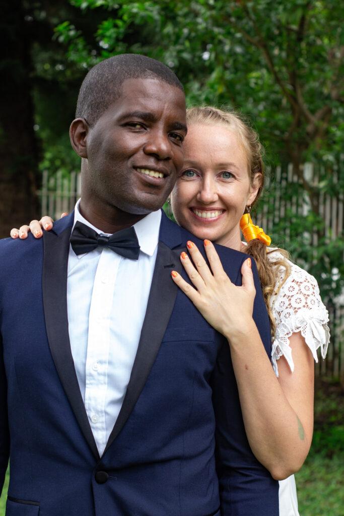 Zuzana s manželem Chrisem, oba ve slavnostním oblečení, na pozadí stromy a bílý plot.