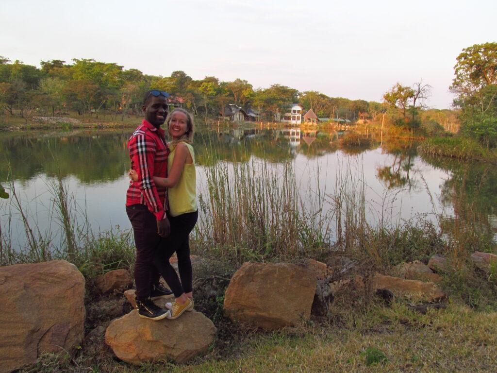 Zuzana a Chris, stojící na kameni, v pozadí jezero nebo rybník.