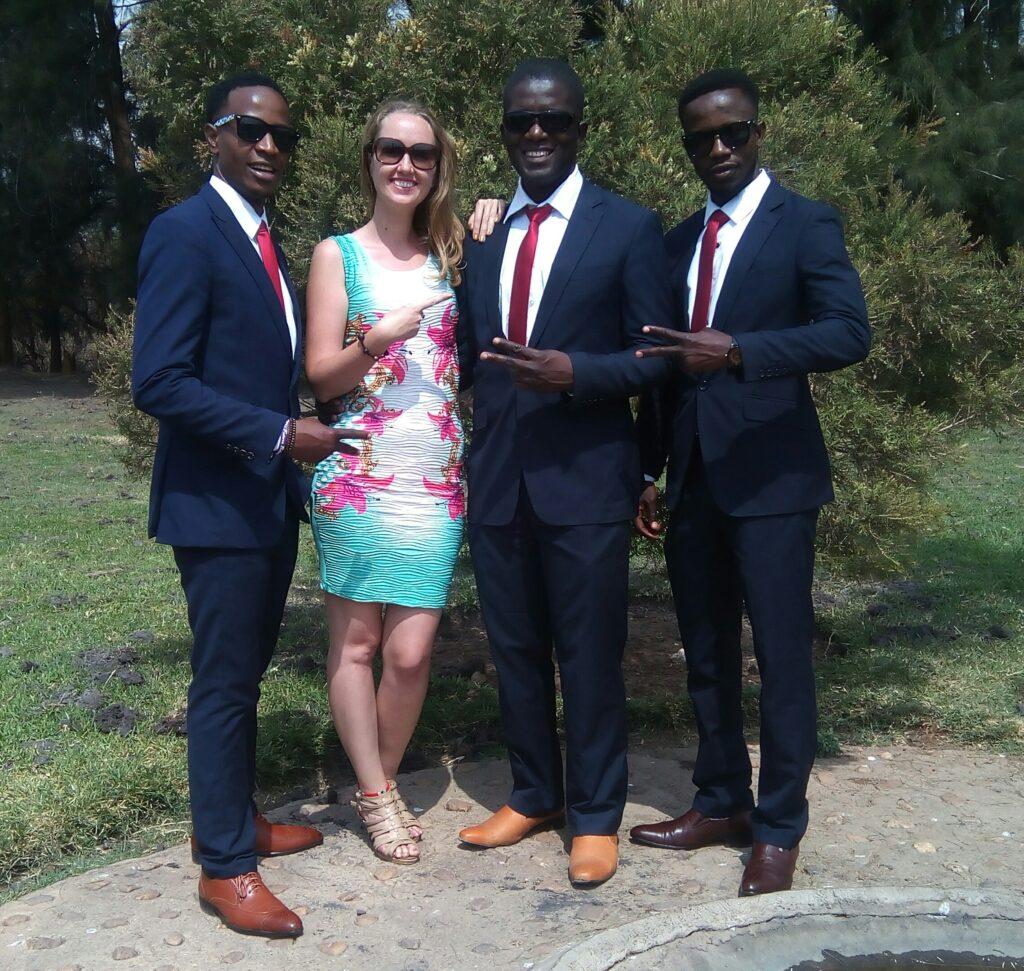 Zuzana s Chrisem a dvěma africkými přáteli, všichni v saku, Zuzana v šatech.
