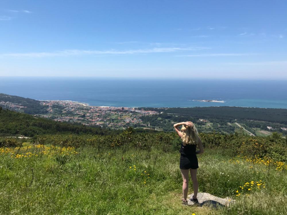 Dominika se dívá směrem k moři, stojí na louce, před ní město na pláži