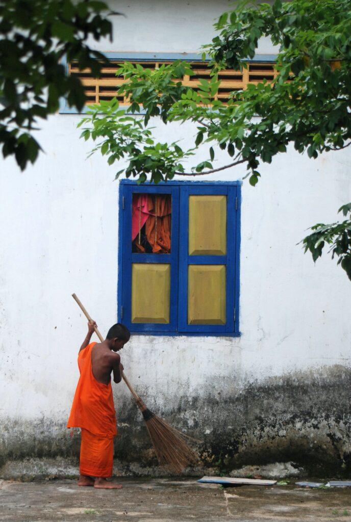 Mnich v oranžovém hávu, zametající před bílým domkem s modrým oknem.
