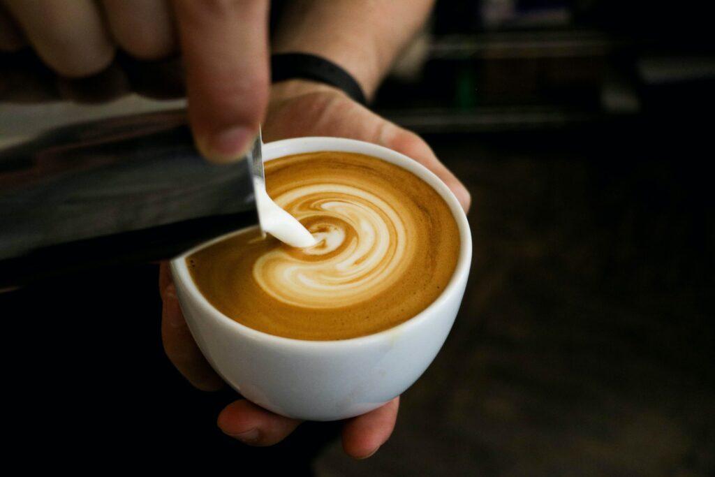 Latte art na cappuccinu, konvička s mlékem a šálek