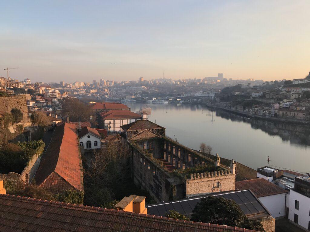 Portugalské město, v popředí historická část, vedle ní řeka a v pozadí zbytek města