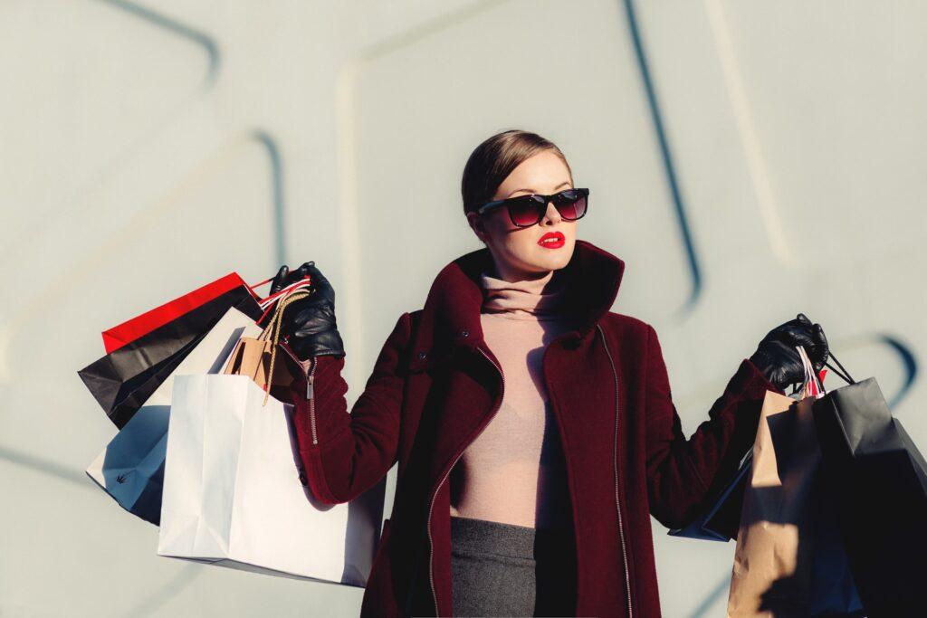 Výrazně namalovaná žena, nesoucí spoustu nákupních tašek