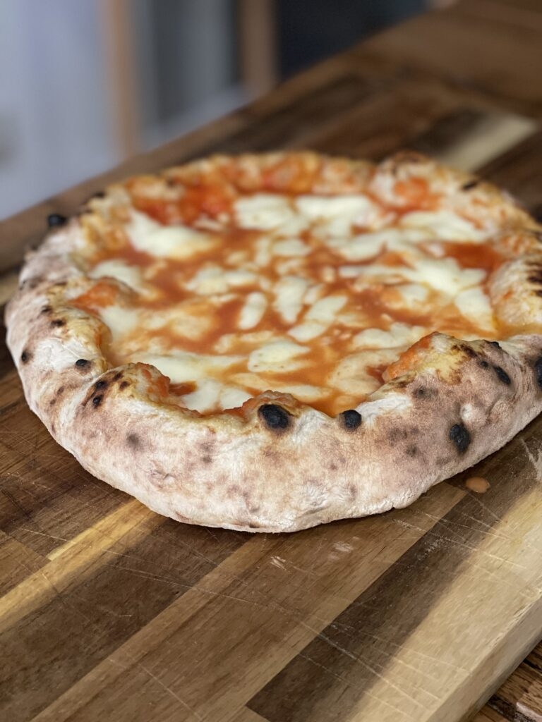 Italská pizza, ležící na dřevěném stole