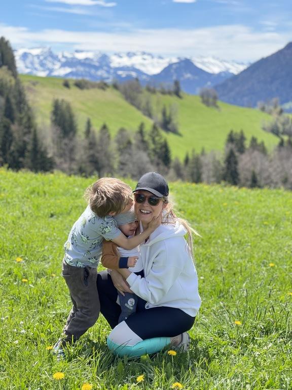 Klára s dětmi na louce, v pozadí švýcarské hory