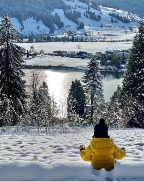 Klářino dítě, zabořené ve sněhu až po pas, na pozadí voda a hory.