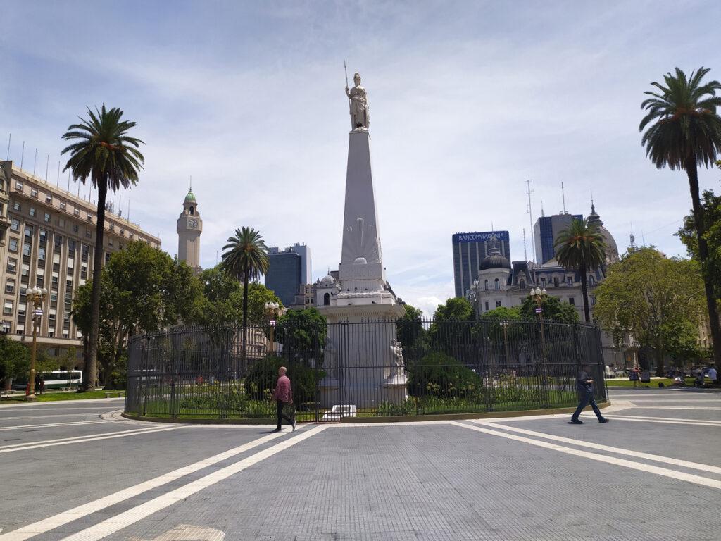 Socha uprostřed náměstí, okolo palmy