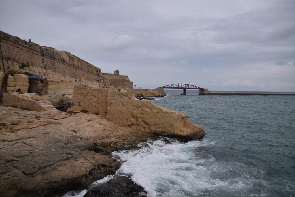 Pohled na moře, kamenitá pláž a zatažená obloha