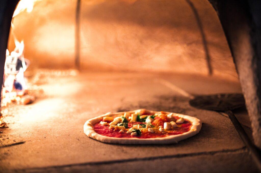 pizza v peci, v pozadí oheň